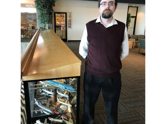 Benjamin Donnelly, an adjunct history professor at the University of Great Falls, poses next to one of two cases at the Great Falls International Airport that house the Poletto Collection, consisting of hundreds of model airliners crafted by his stepfather, Bary Poletto.