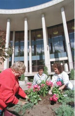 Members of the Great Falls Flower Growers club, from left, Delores Gregory, Shu Mae Black and Cheryl Hirose plant flowers in a planter outside of the Great Falls Public Library on May 22, 1998.
