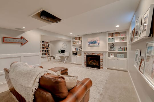 The lower level living area has new built-in shelves, library noon and library shelves, a gas fireplace, surround sound with hidden speakers and a projector.