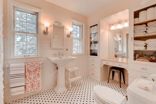 The main floor bath has penny-size tile floors, vanity, and built-in shelves, cabinets and drawers for storage.