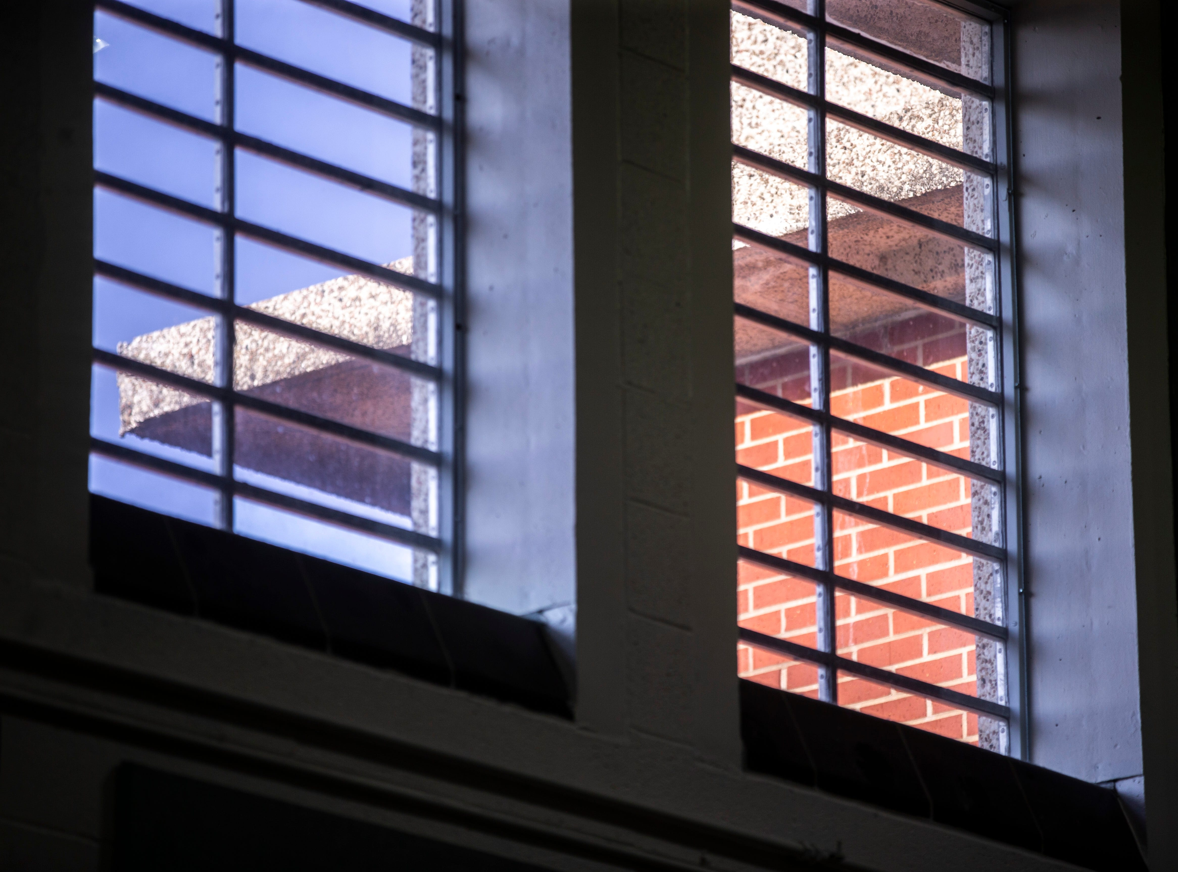 Light sines on the brick of the building outside a window in the gym during an Oakdale Community Choir practice on Tuesday, April 16, 2019, at Oakdale Prison in Coralville, Iowa.