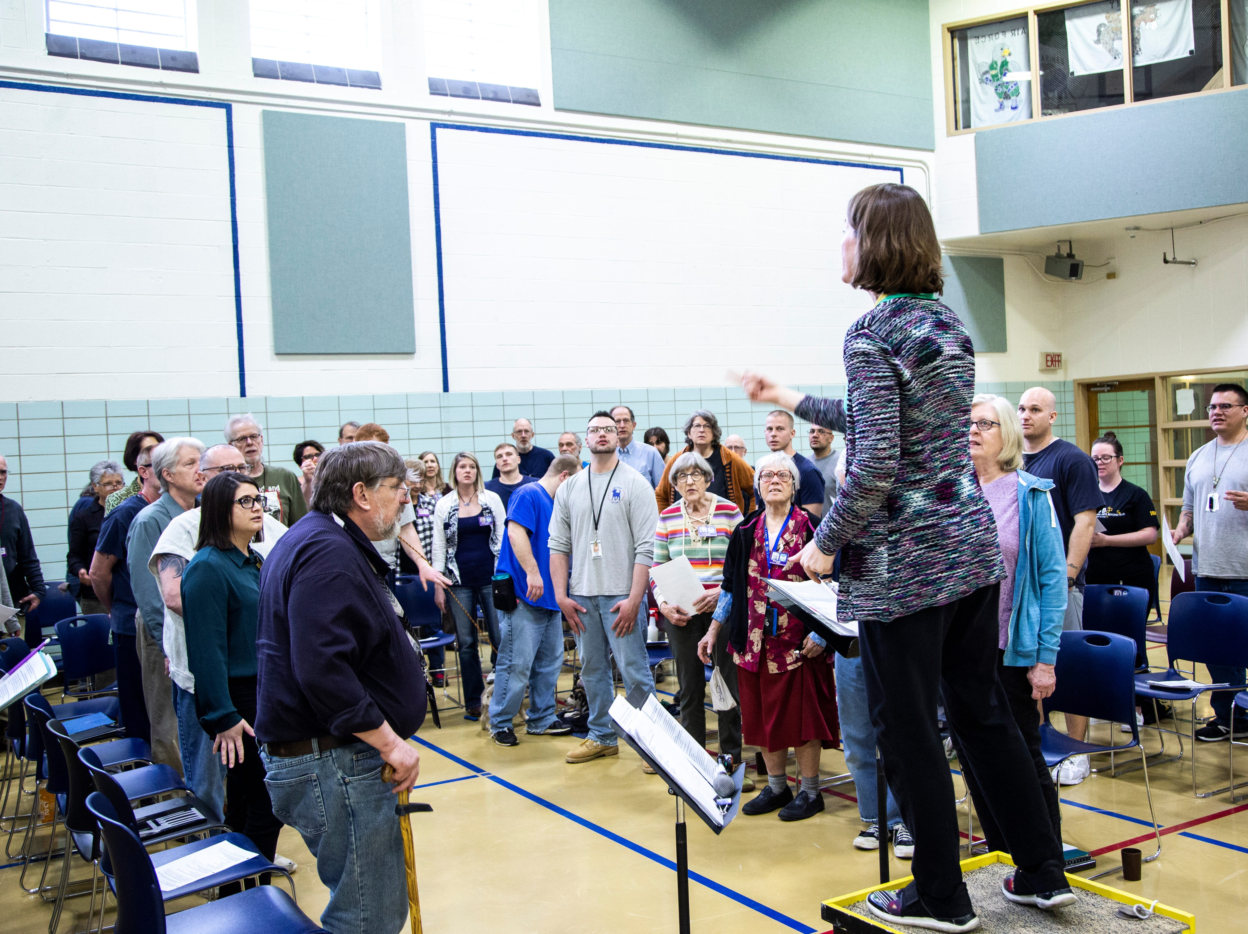 Mary Cohen, an associate professor of music education at the University of Iowa, conducts during an Oakdale Community Choir practice on Tuesday, April 16, 2019, at Oakdale Prison in Coralville, Iowa.