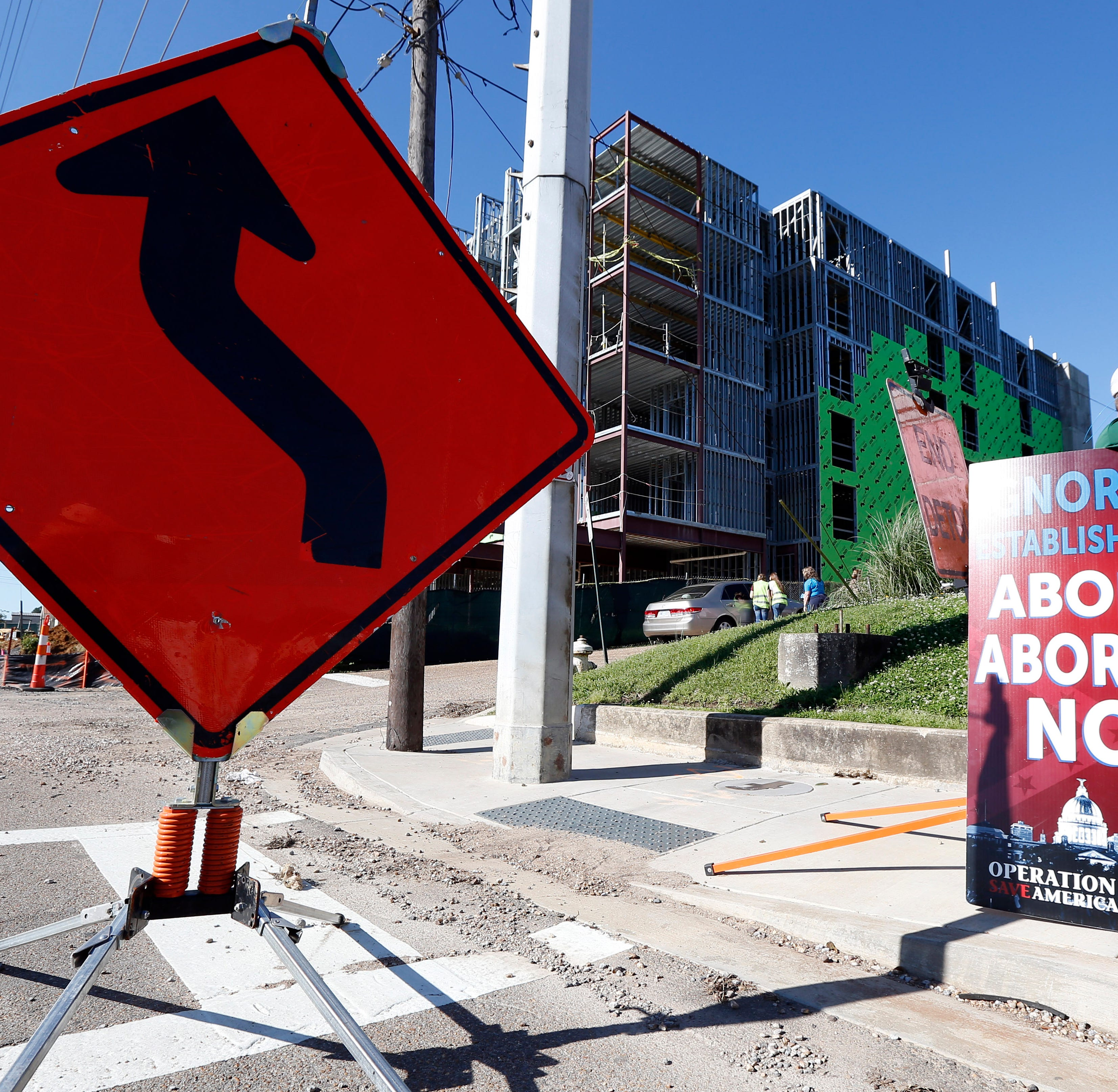 Abortion opponents stand outside the Jackson Women's Health Organization clinic, right, while construction on a hotel, background, continues in Jackson, Miss., Wednesday, April 10, 2019. The clinic is the only medical facility that performs abortions in the state. The state legislature recently passed a law that would ban most abortions after a fetal heartbeat is detected, meaning as early as six weeks.