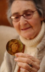 Auschwitz survivor Mira Kimmelman holds a photograph of herself taken as a child that her father carried in a lapel badge in 2005.