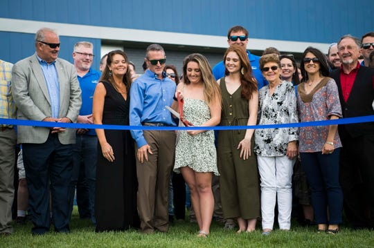 Workers and local officials watch as Baylee Bohanan, youngest daughter of Protomet CEO and founder Jeff Bohanan, cuts the ribbon at the official opening of Protomet's Loudon County plant Thursday, April 18, 2019.