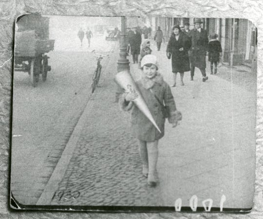 Mira Ryczke of Danzig carries a large cone of candy given out on the first day of school. This photo was hidden in a canteen and outlasted the Nazi concentration camps.