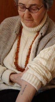 Auschwitz survivor Mira Kimmelman shows the tattooed number on her forearm.