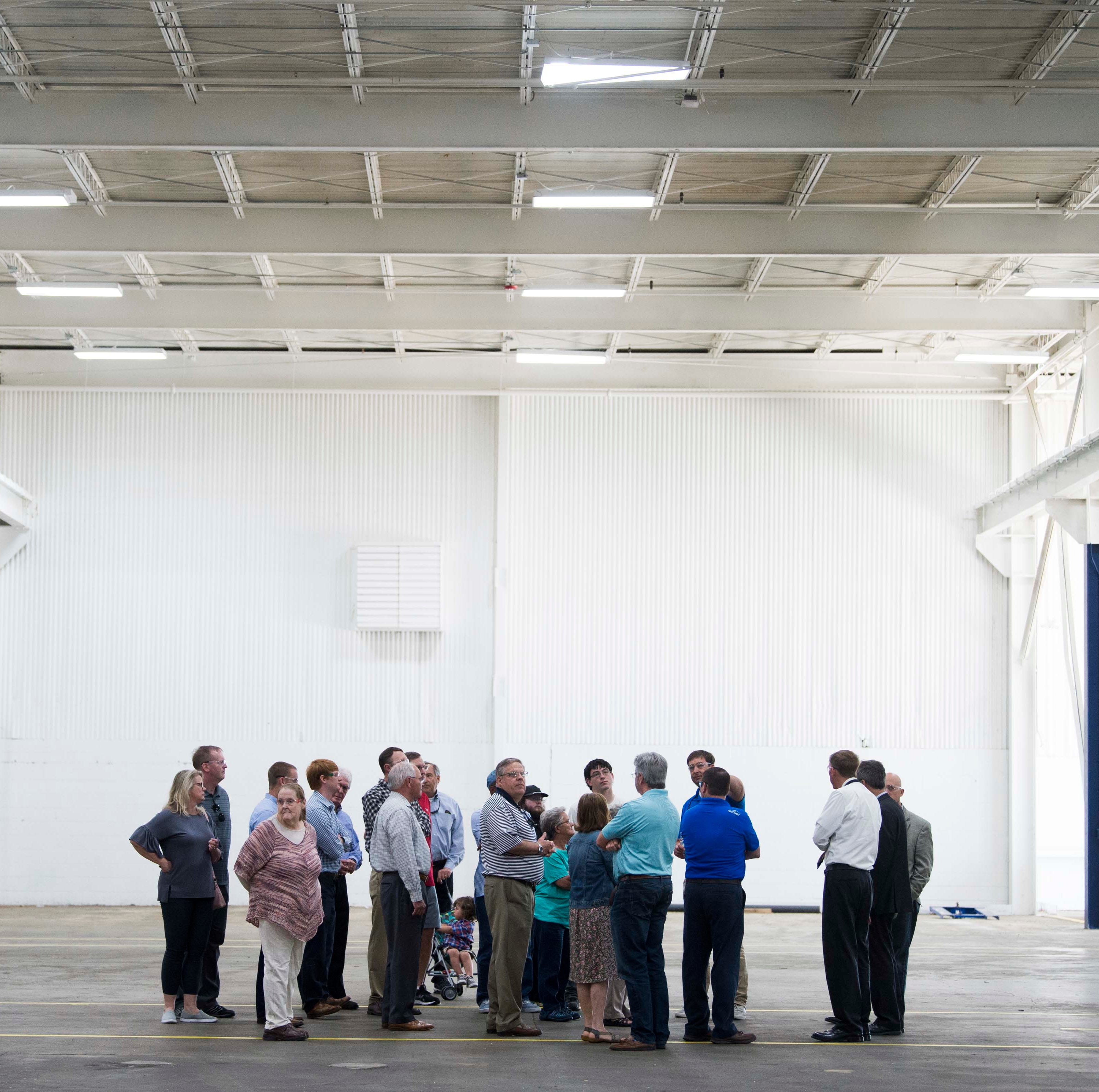 Local officials and visitors tour the opening of...