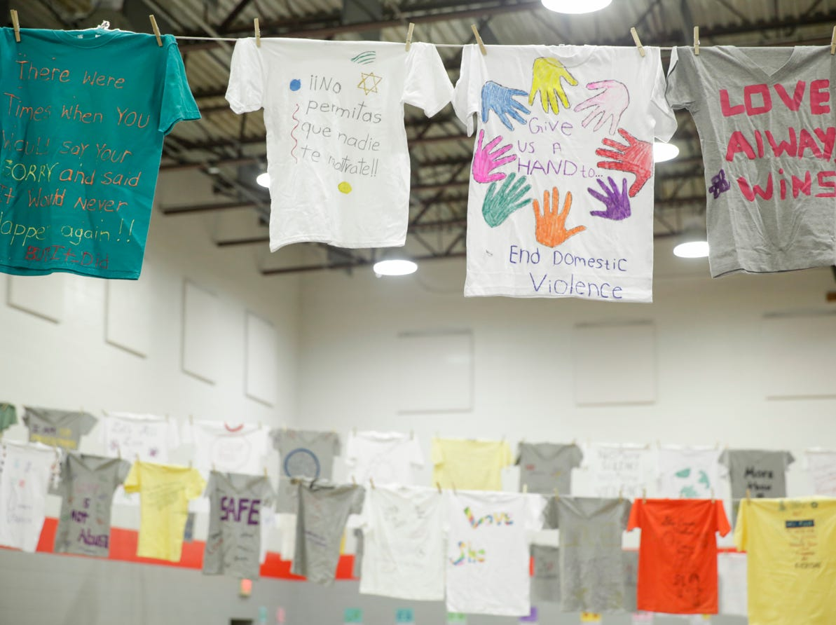 T-shirts with messages from domestic violence survivors hang above quests during the 18th annual Clay Bowl Giving Project, Thursday, April 18, 2019 at the YWCA Greater Lafayette in Lafayette. Local potters donated the clay bowls. The event benefits YWCA's Domestic Violence Intervention and Prevention Program.
