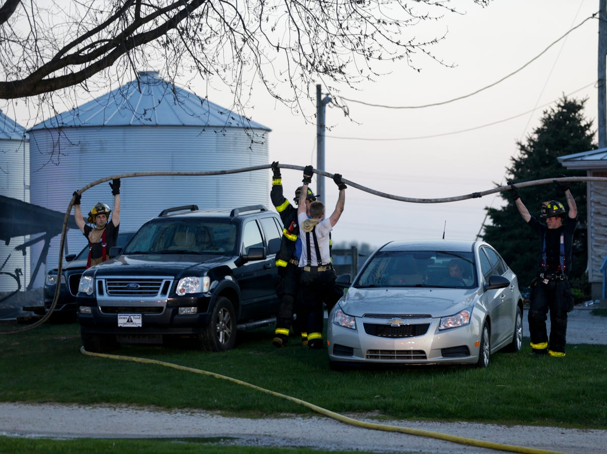 Fire fighters lift a hose over cars as they work to clear the scene of a structure fire on the 5300 block of Jackson Highway, Wednesday, April 17, 2019 in Wabash Township.