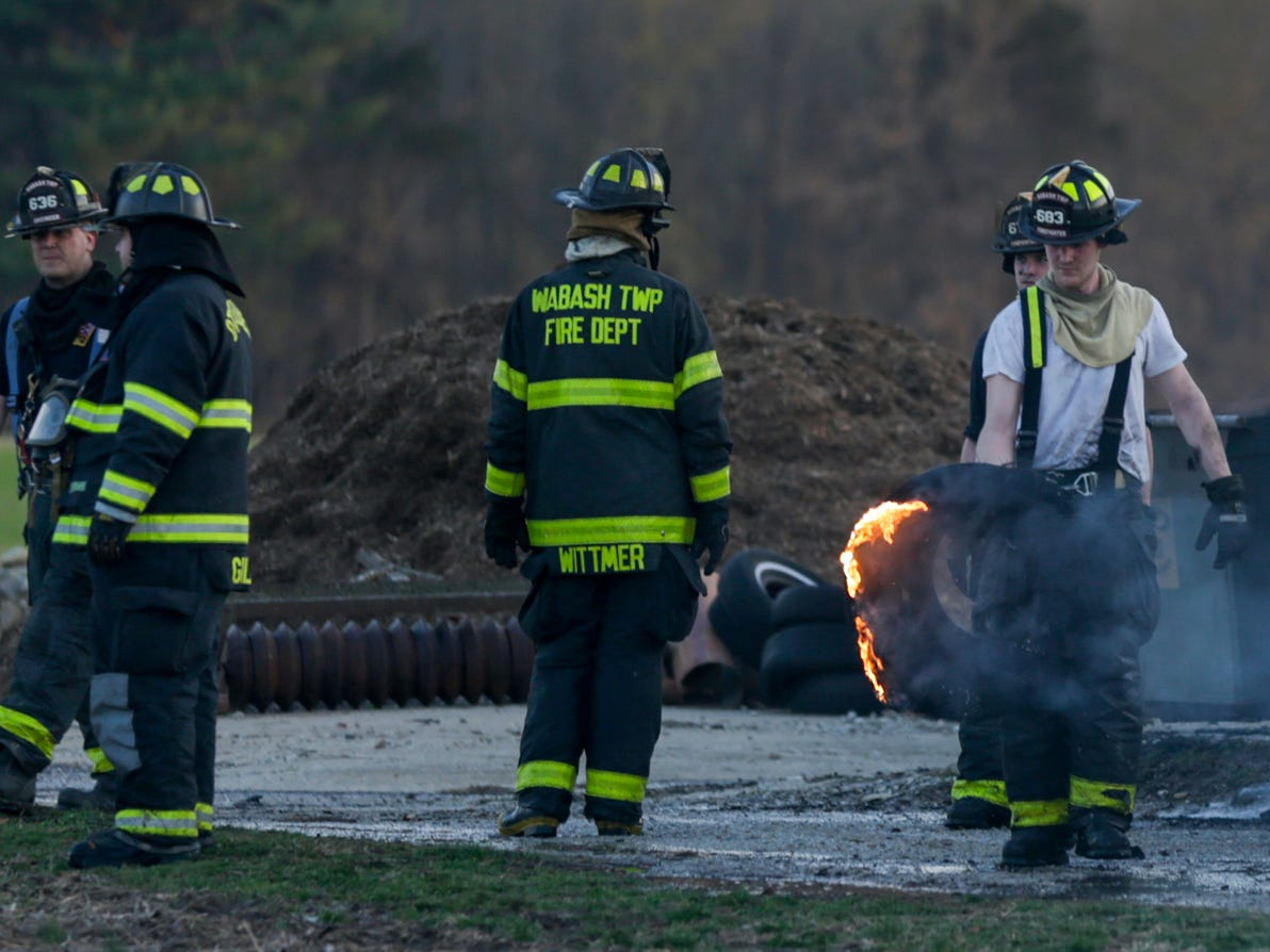 A fire fighter carries a flaming tire towards a pool of water to extinguish the flames at the scene of a structure fire on the 5300 block of Jackson Highway, Wednesday, April 17, 2019 in Wabash Township.