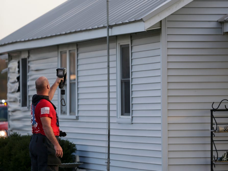 A fire fighters uses a thermal imaging camera to check a house for hot spots as crews work the scene of a structure fire on the 5300 block of Jackson Highway, Wednesday, April 17, 2019 in Wabash Township.