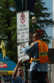 In this May 1, 2006 file photo, Shane Menard, bottom, and Cedric Wiltz, top, remove the no parking signs, Monday May 1, 2006, on Jefferson St. after Festival International de Louisiane wrapped up.