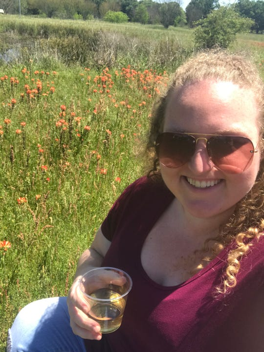 Reporter Ashley White snaps a photo in the wildflowers at Peach Creek Vineyards in College Station, Texas, at an event Sunday, April 14, in conjunction with Bluebonnet Hills Alpaca Ranch.
