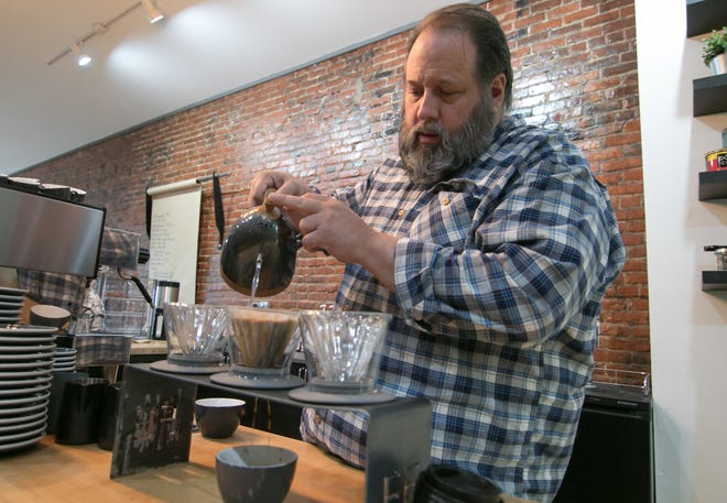 Kevin Ridge, owner of Black Iron Coffee Roasters, performs a 'pour-over' Thursday, April 18, 2019, pouring water into a filtered funnel containing coffee grounds, which then drip into the cup below.