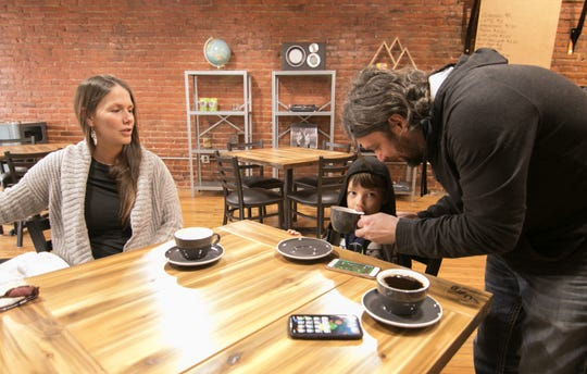 August Krys helps his 5-year-old son Emmett Krys with his hot chocolate while Emmett's mom Andrea keeps a hand on 4-month-old Annabelle (not pictured) at Black Iron Coffee Roasters in downtown Howell Thursday, April 18, 2019.