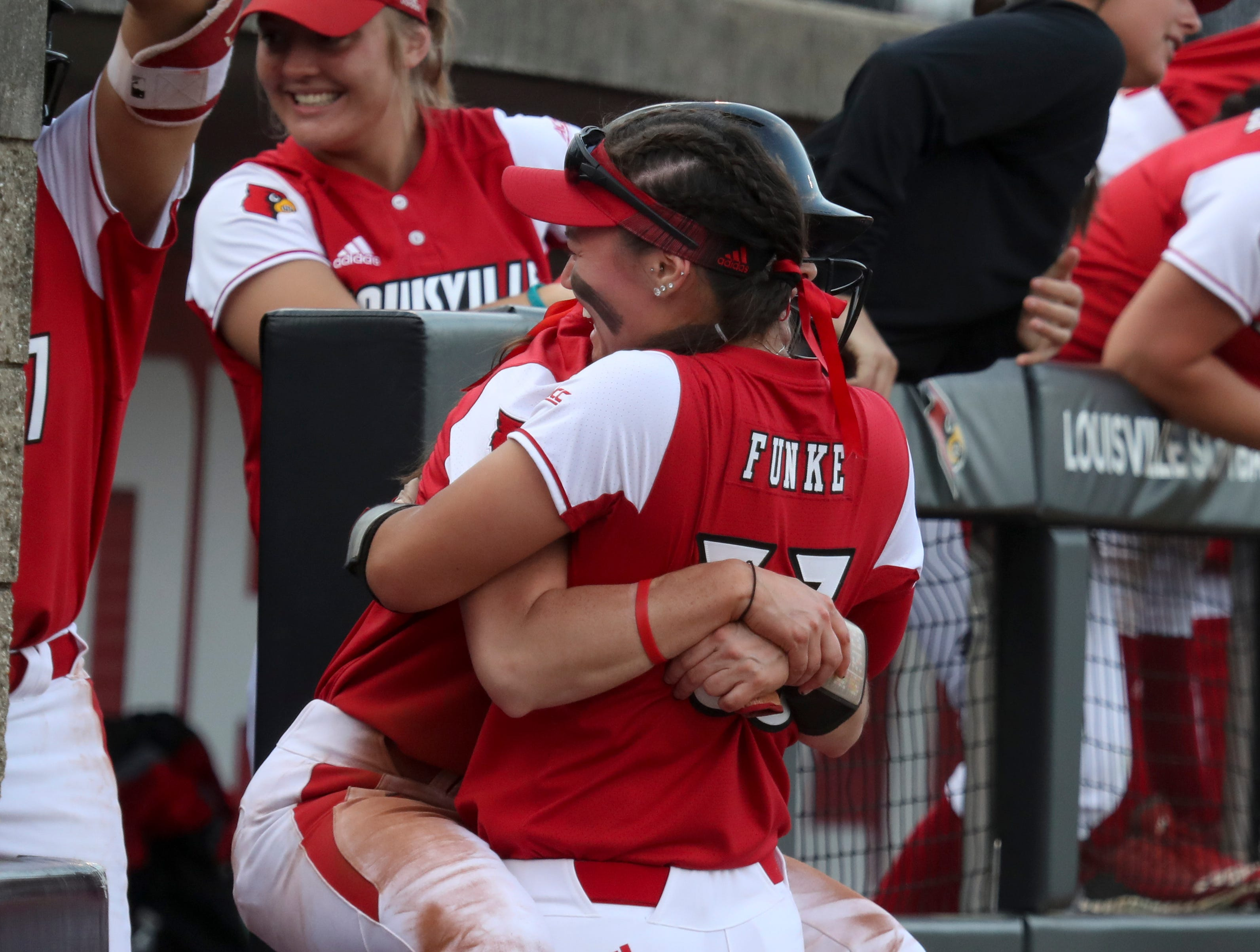 Louisville's Celene Funke and teammates celebrate another run against Kentucky on April 17.