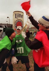 """Dressed as M & M candies for Halloween, Michigan State University  students Daniel Reese, Joseph Lozon and Troy Falko, left to right, all 22, drink beer from a """"beer bong"""" as they tailgate on campus before a football game. An MSU social norms marketing campaign is credited for limiting high-risk drinking at MSU."""