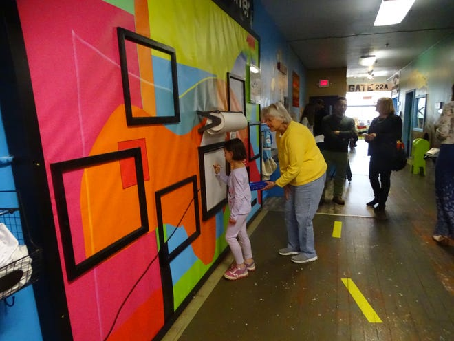 Riley Esterline, 7, of Mansfield, draws a unicorn bunny rabbit at the newly revamped art wall at Little Buckeye Childrens Museum on West Fourth Street provided by the Mansfield Art Center. With her is grandmother Ursula Esterline.