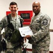 Alex Popoff receives a letter of appreciation from a Senior Master Sergeant for detaining two individuals with warrants out for drugs and violence.