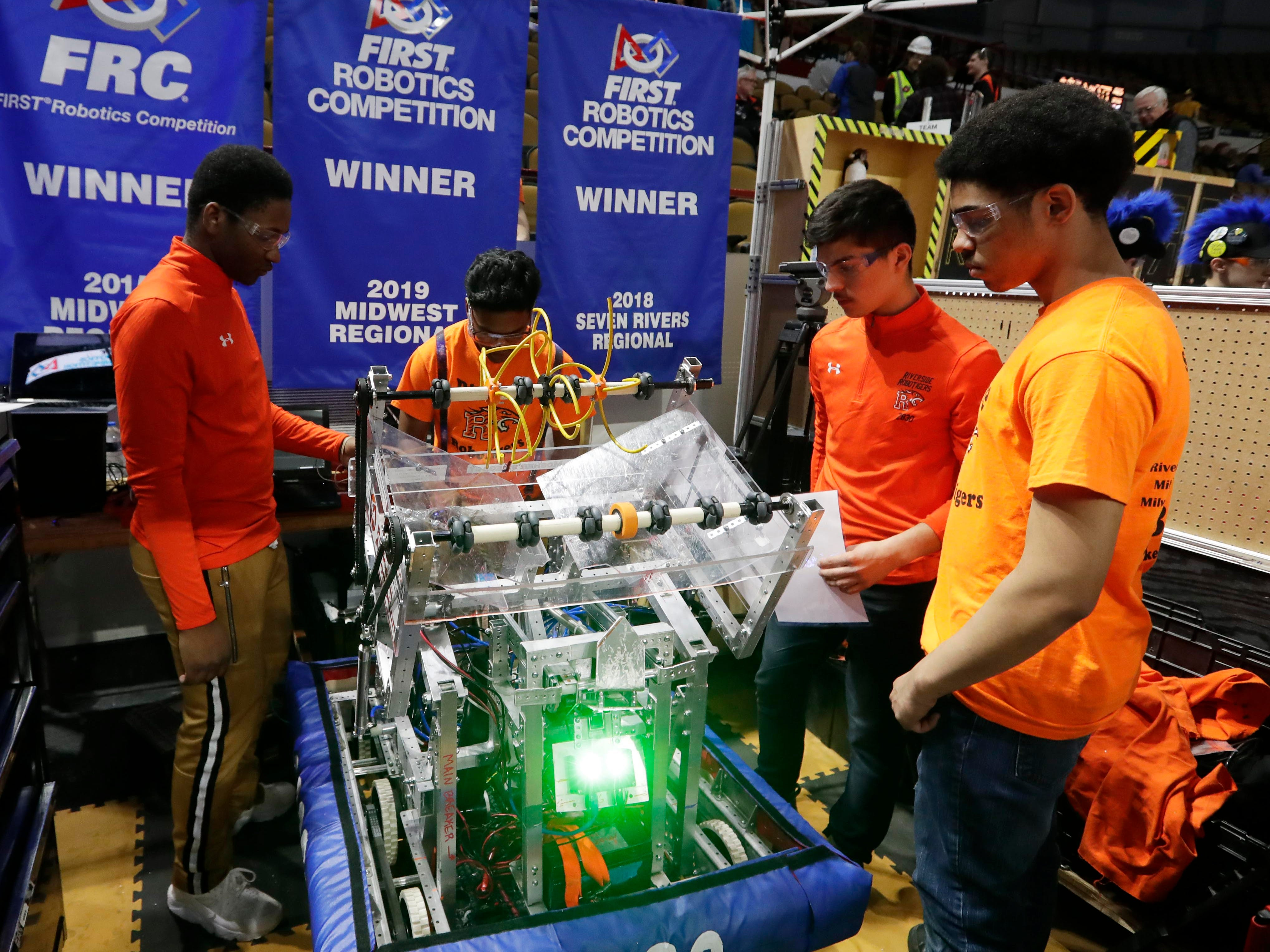 Riverside RoboTigers pit crew team members Abdullah Abdi, Yannang Soe, Eduardo Hernandez,  inspect the robot and fix any problems between competitions. Abdi, the team captain, is a Kenyan refugee who didn't know any English when he came to Milwaukee four years ago.