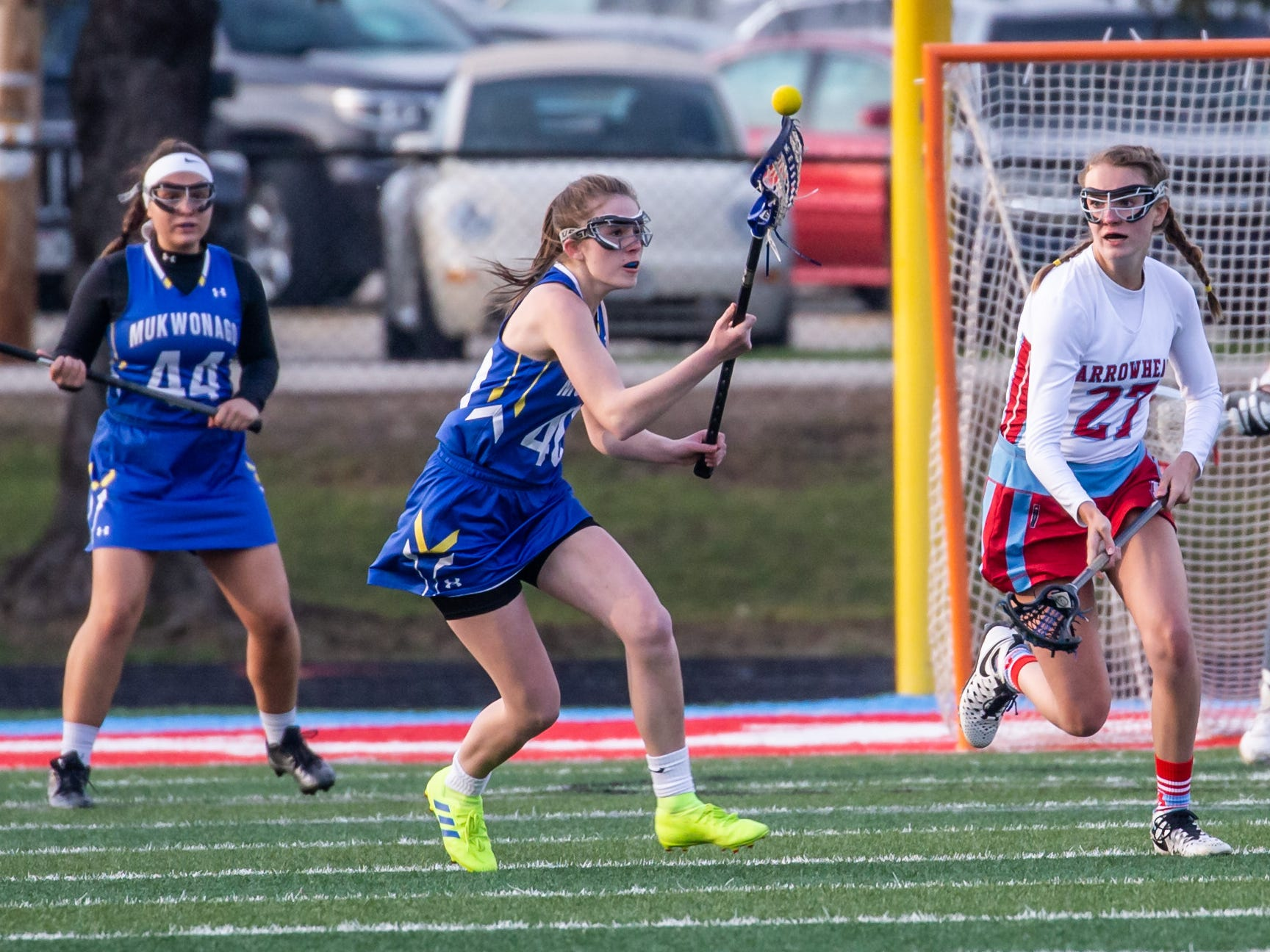 Mukwonago's Sarah Burton (40) scoops up a loose ball during the game at Arrowhead on Tuesday, April 16, 2019.