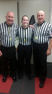 Referees (from left) Nick LoCicero, Abby Burmeister and Mike Steidl pose before officiating a game with yellow whistles during the Yellow Whistles for Greg campaign.