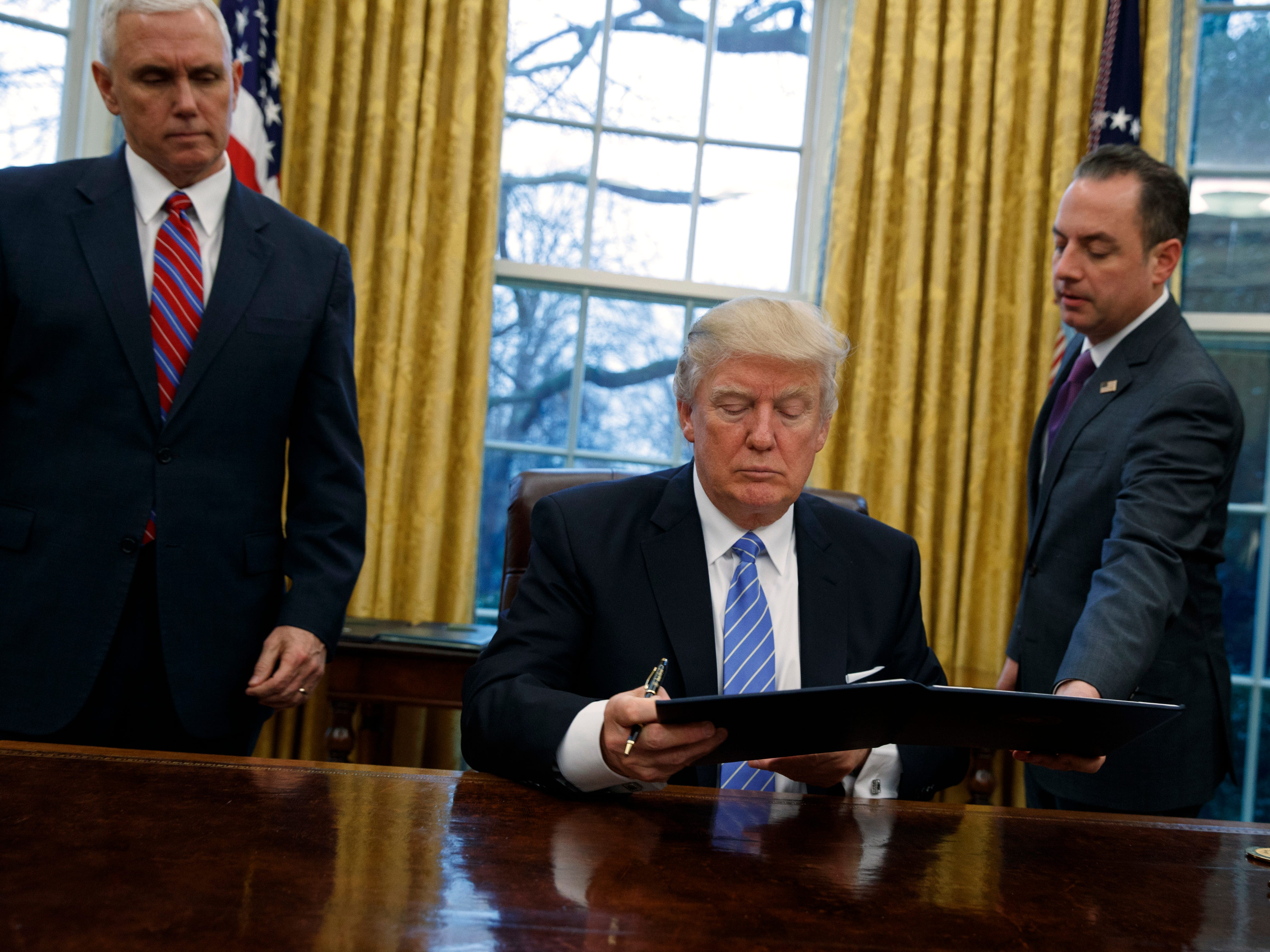 Vice President Mike Pence watches (left) as White House Chief of Staff Reince Priebus hands an executive order to withdraw the U.S. from the 12-nation Trans-Pacific Partnership trade pact to President Donald Trump.