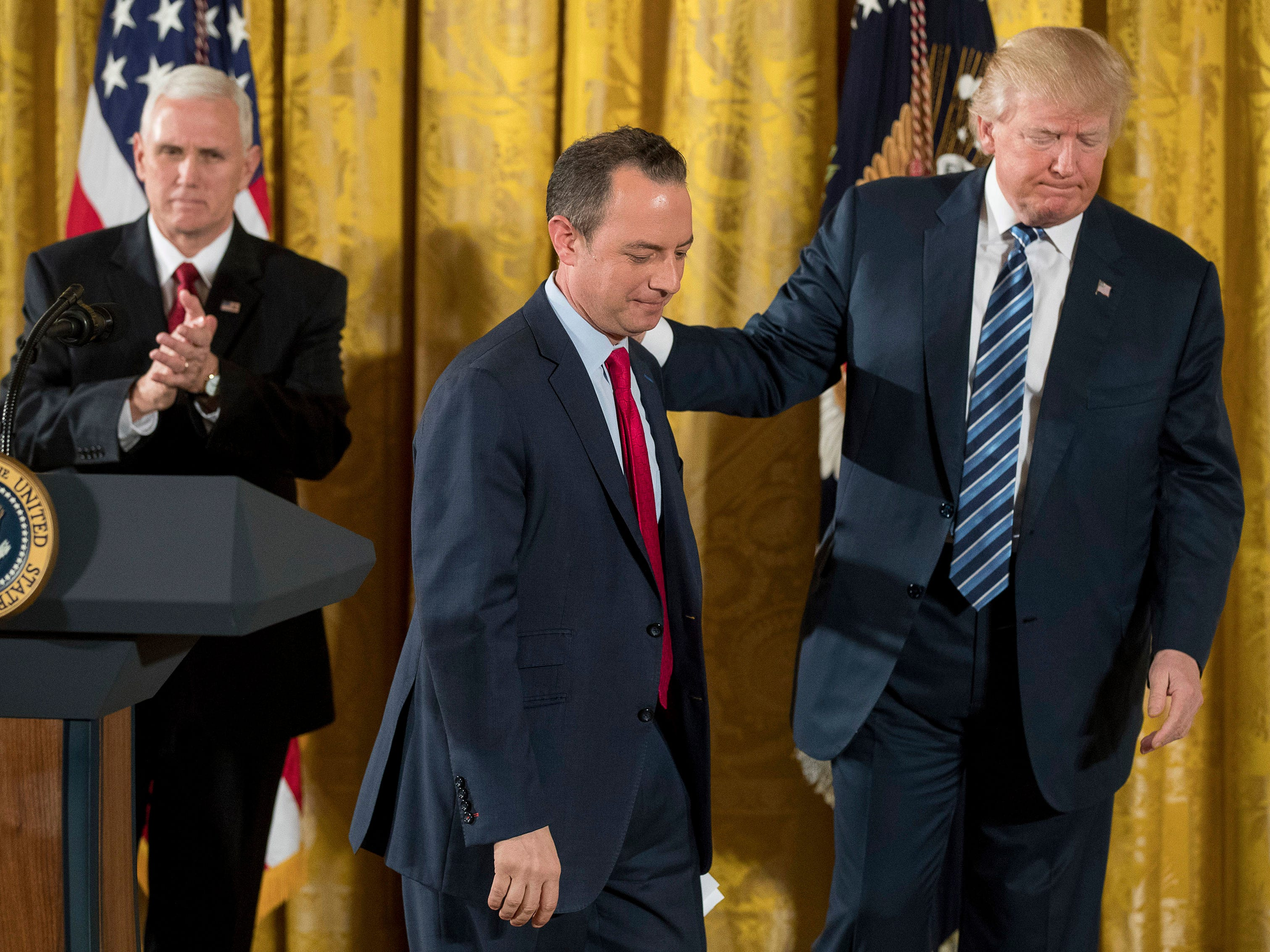 Trump Chief of Staff Reince Priebus (center), accompanied by Vice President Mike Pence (left), and President Donald Trump, leaves the stage after speaking during a White House senior staff swearing in ceremony in the East Room of the White House
