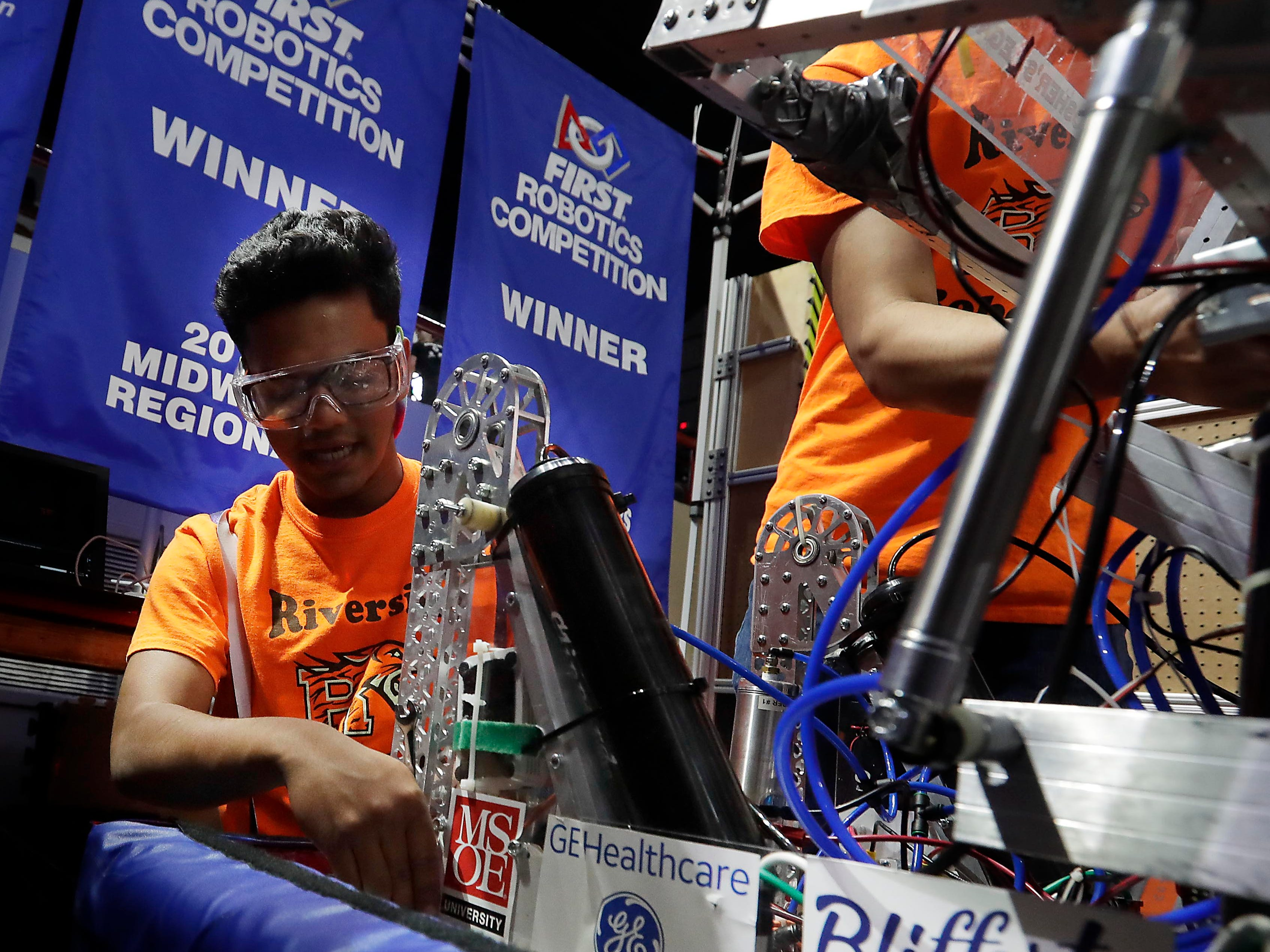 Riverside RoboTigers pit crew team member Yannang Soe tightens a connection on the robot between competitions.