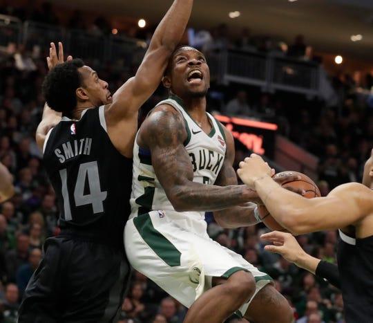 Bucks guard Eric Bledsoe  scores under the basket against Detroit Pistons guard Ish Smith on Wednesday night.