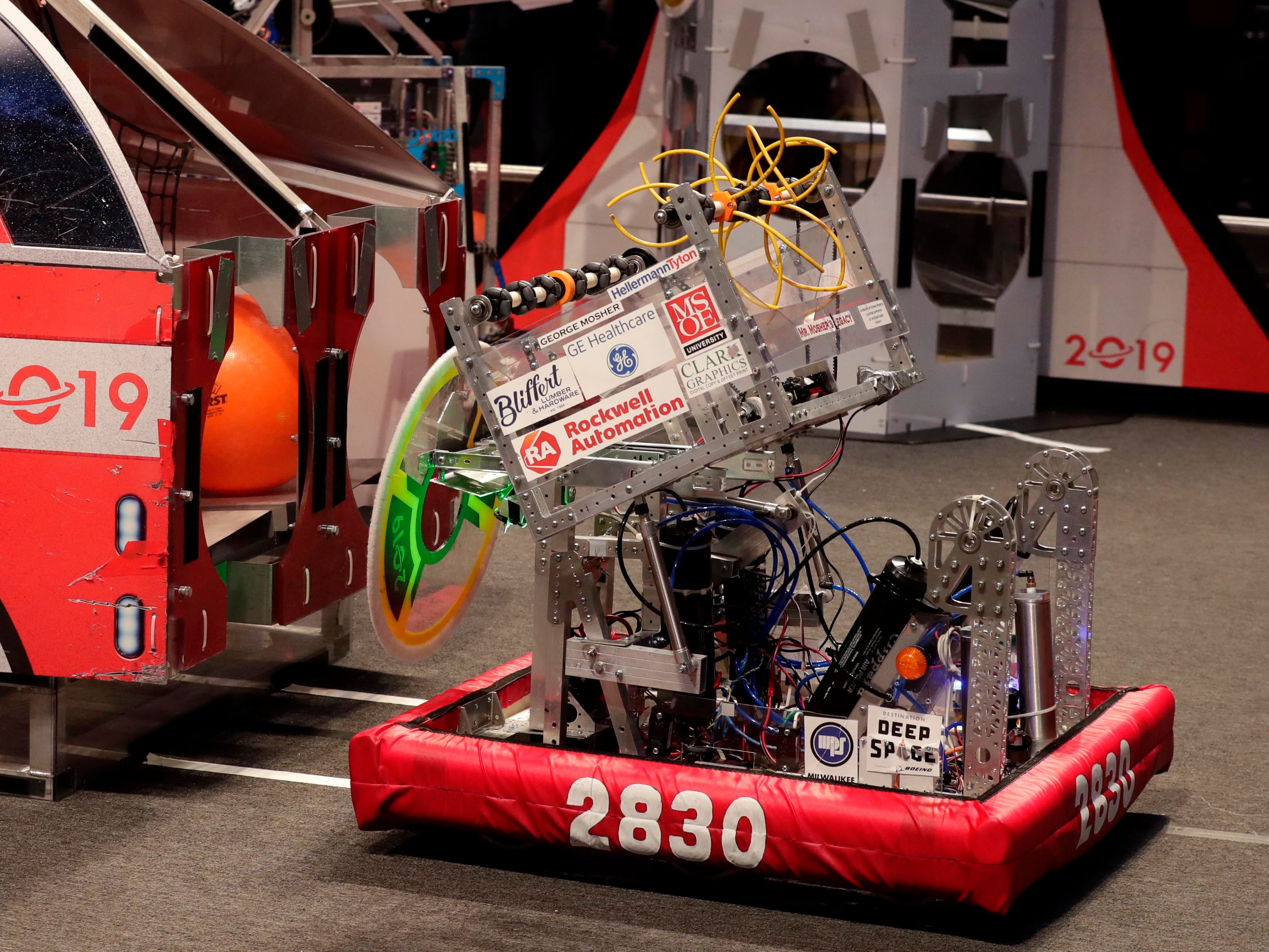 Team members  maneuver their robot to attach a circular disk to a magnet to score points during competition.