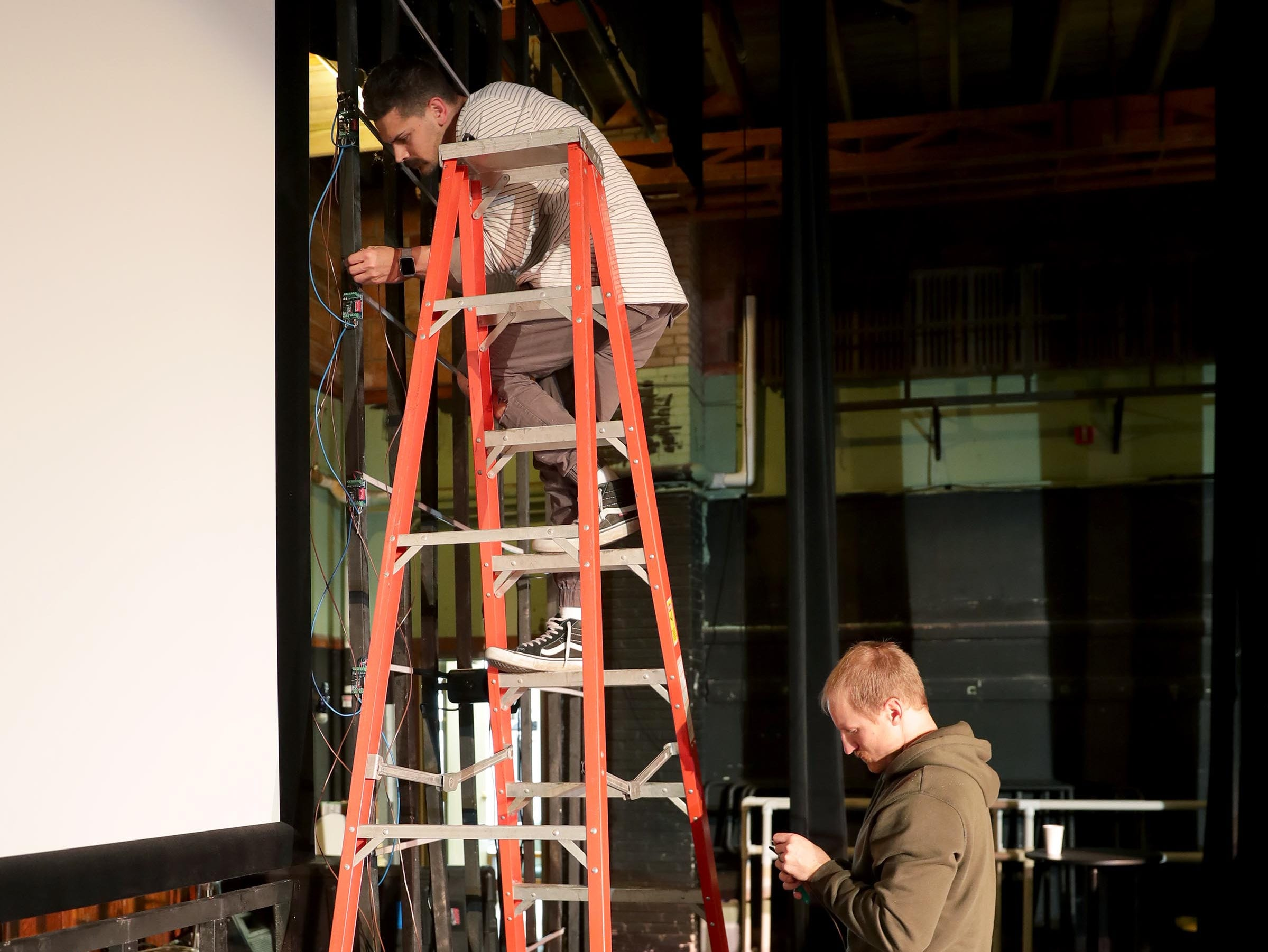 Josh Palasz, upper, Cornerstone Church creative director, and associate pastor Andrew Hess work on hooking up lighting to the stage area at Lincoln Center of the Arts on East Knapp Street where they will host their Easter Sunday service.
