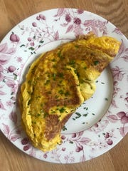 Additional fresh minced chives are sprinkled over the finished omelet.