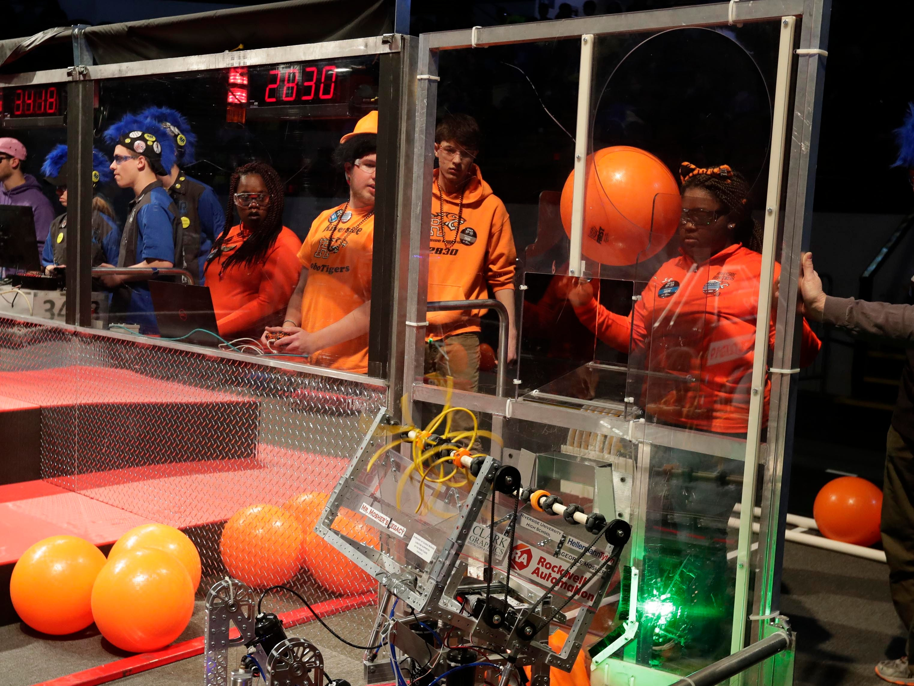 """Team members  Arianna Massey, Damien Berna, Mordechai Tinney  and Mikalayah Tulloch position their 2830 robot  to receive a ball  to move during competition at the U.S. First 2019 Wisconsin Regional Robotics Competition  at the UWM Panther Arena in Milwaukee. The highly successful robotics team, the Riverside High School RoboTigers, is known as the """"the team with girls on it."""""""