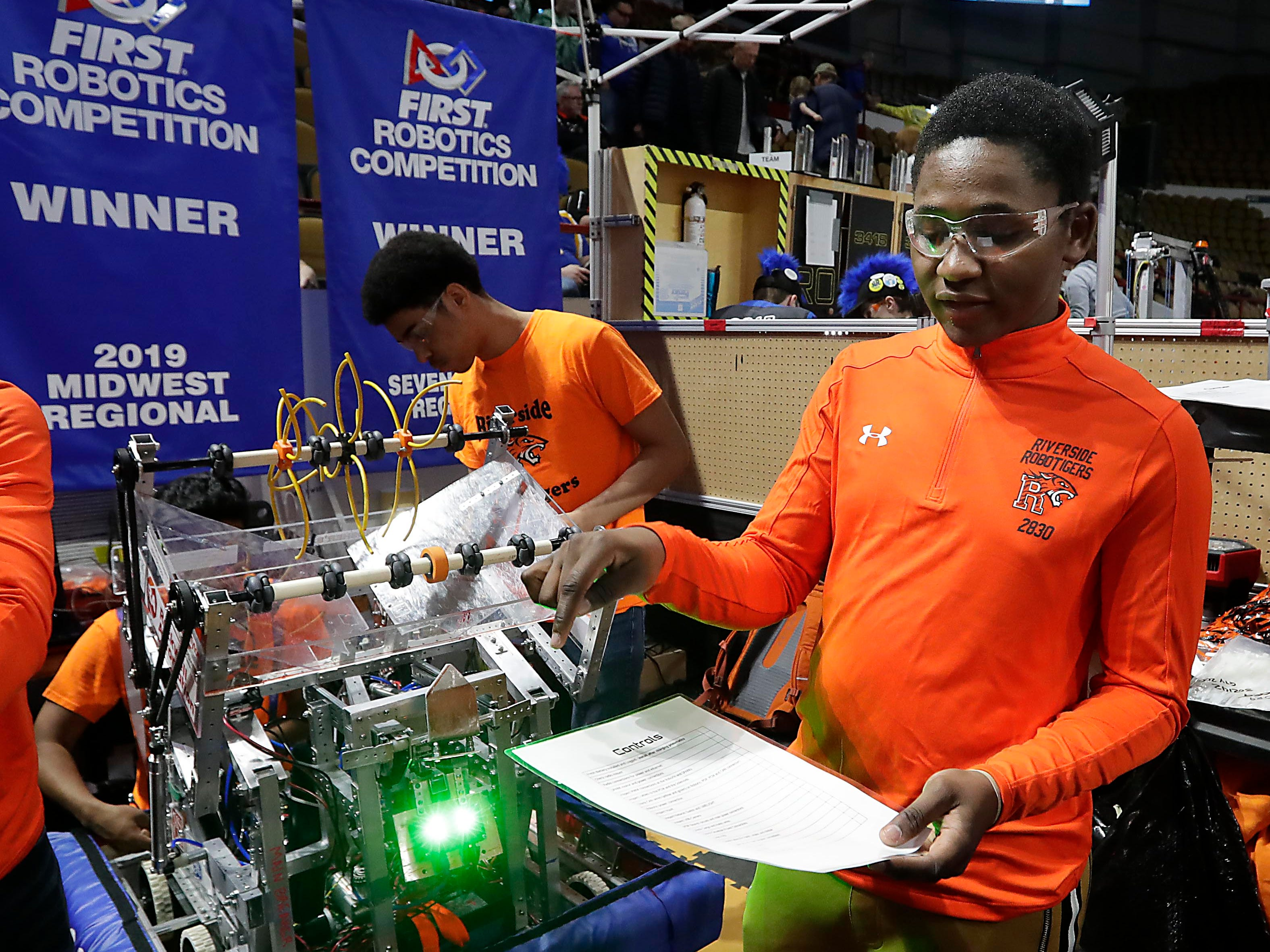 Riverside RoboTigers captain Abdullah Abdi looks at a controls list to check for repairs between competitions.