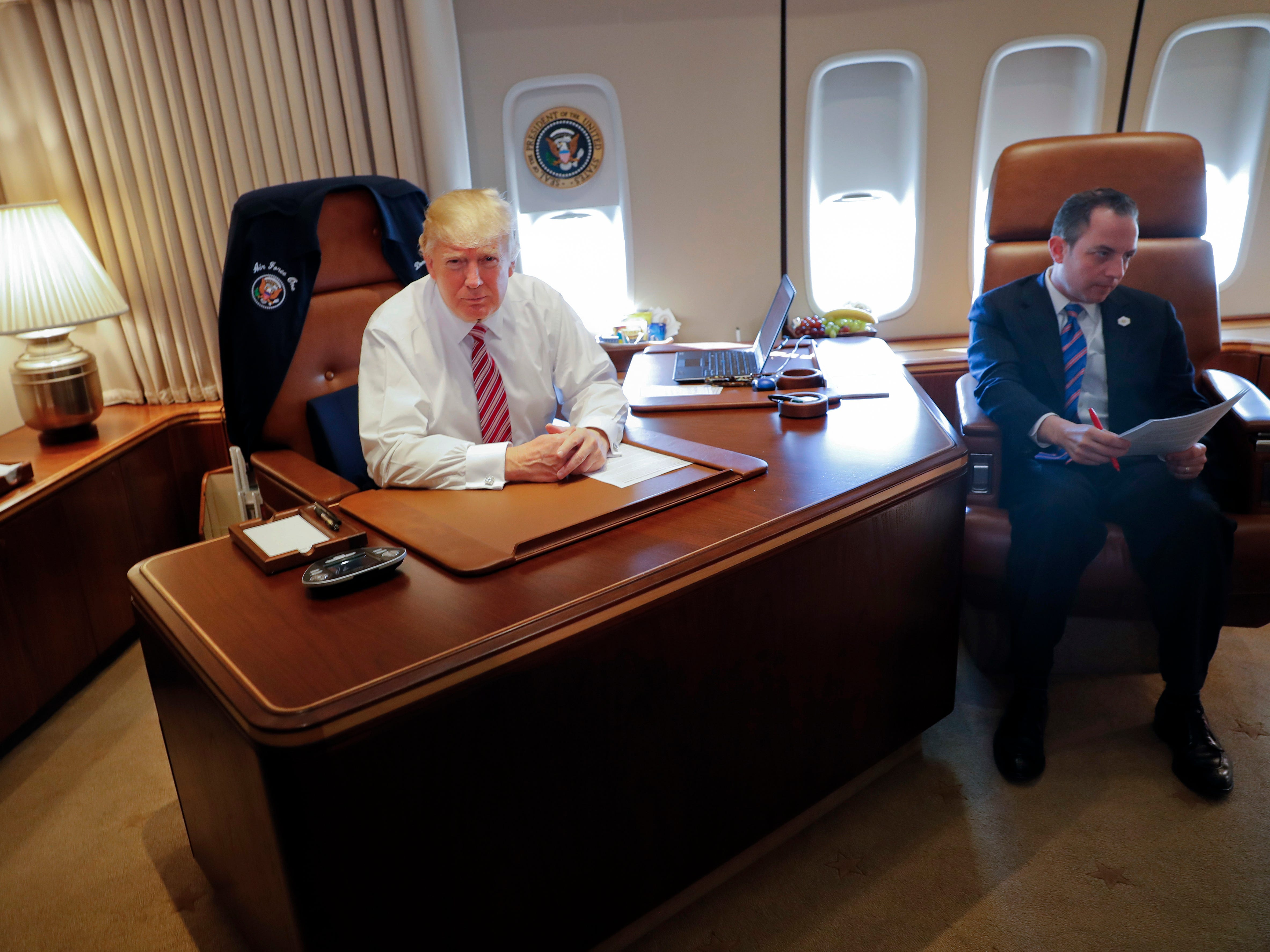 President Donald Trump, with his Chief of Staff Reince Priebus, sits at his desk on Air Force One upon their arrival at Andrews Air Force Base, Md.