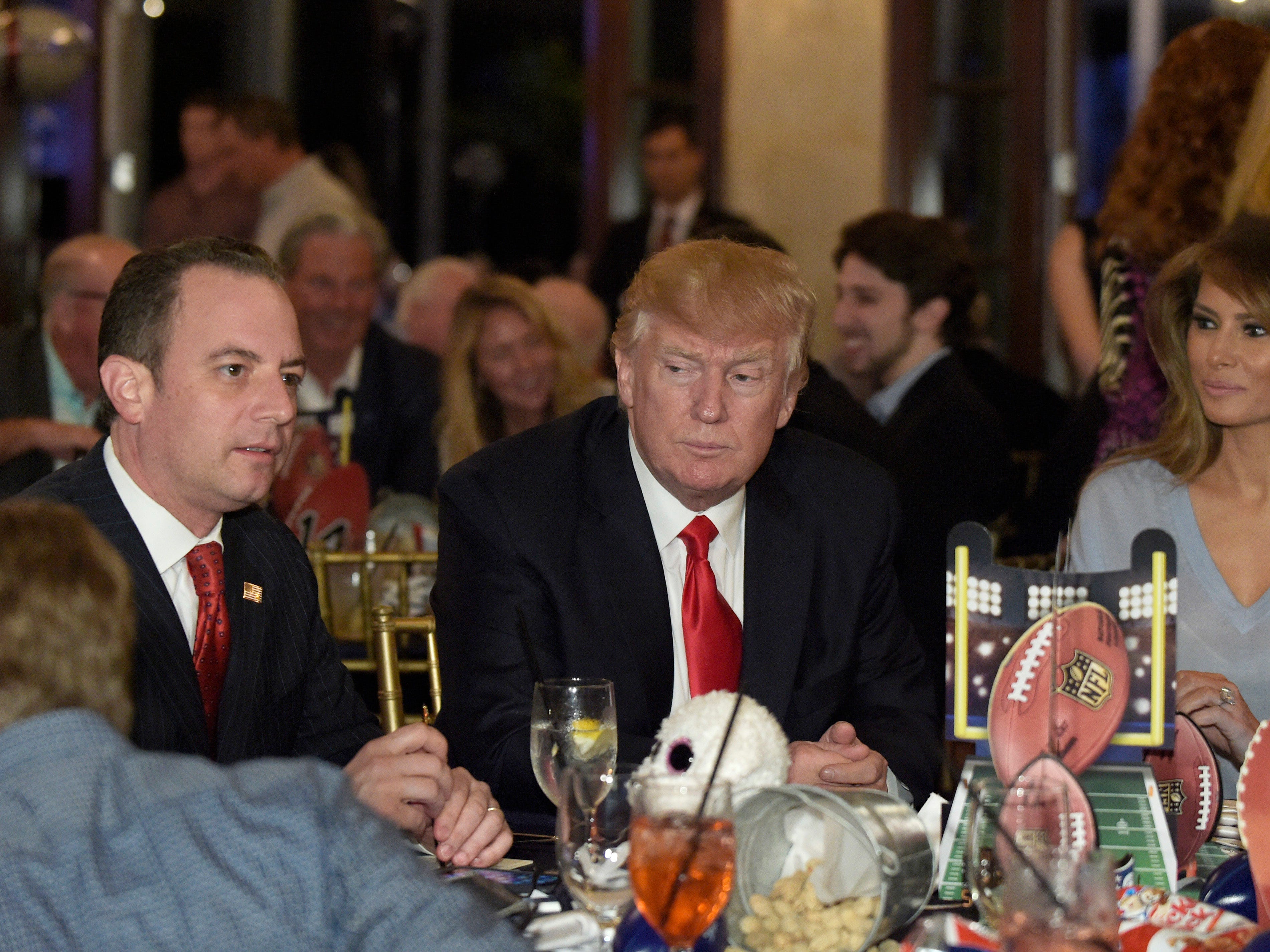 President Donald Trump (center), first lady Melania Trump (second from right), and White House Chief of Staff Reince Priebus attend a Super Bowl party at Trump International Golf Club in West Palm Beach, Fla.