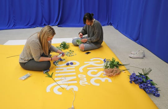 Cornerstone Church member volunteer Danielle Svehlek, left, and Cornerstone Church teams director Eunice Ong work on a photo backdrop at Lincoln Center of the Arts on East Knapp Street in Milwaukee in preparation for the chruch's Easter Sunday service.
