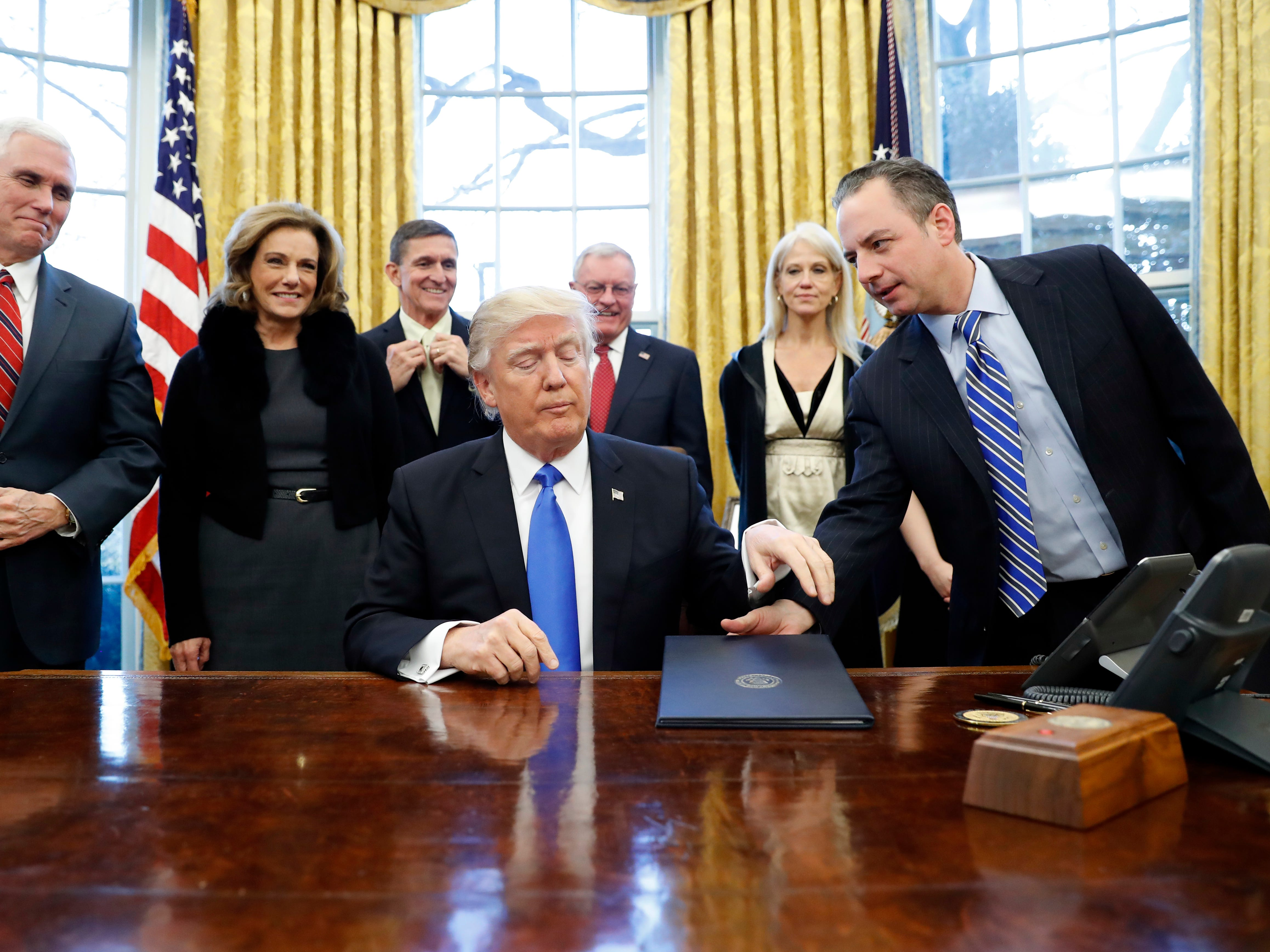 President Donald Trump is handed an Executive Order to sign by White House Chief of Staff Reince Priebus (right), with Vice President Mike Pence (left), and others nearby, in the Oval Office of the White House.