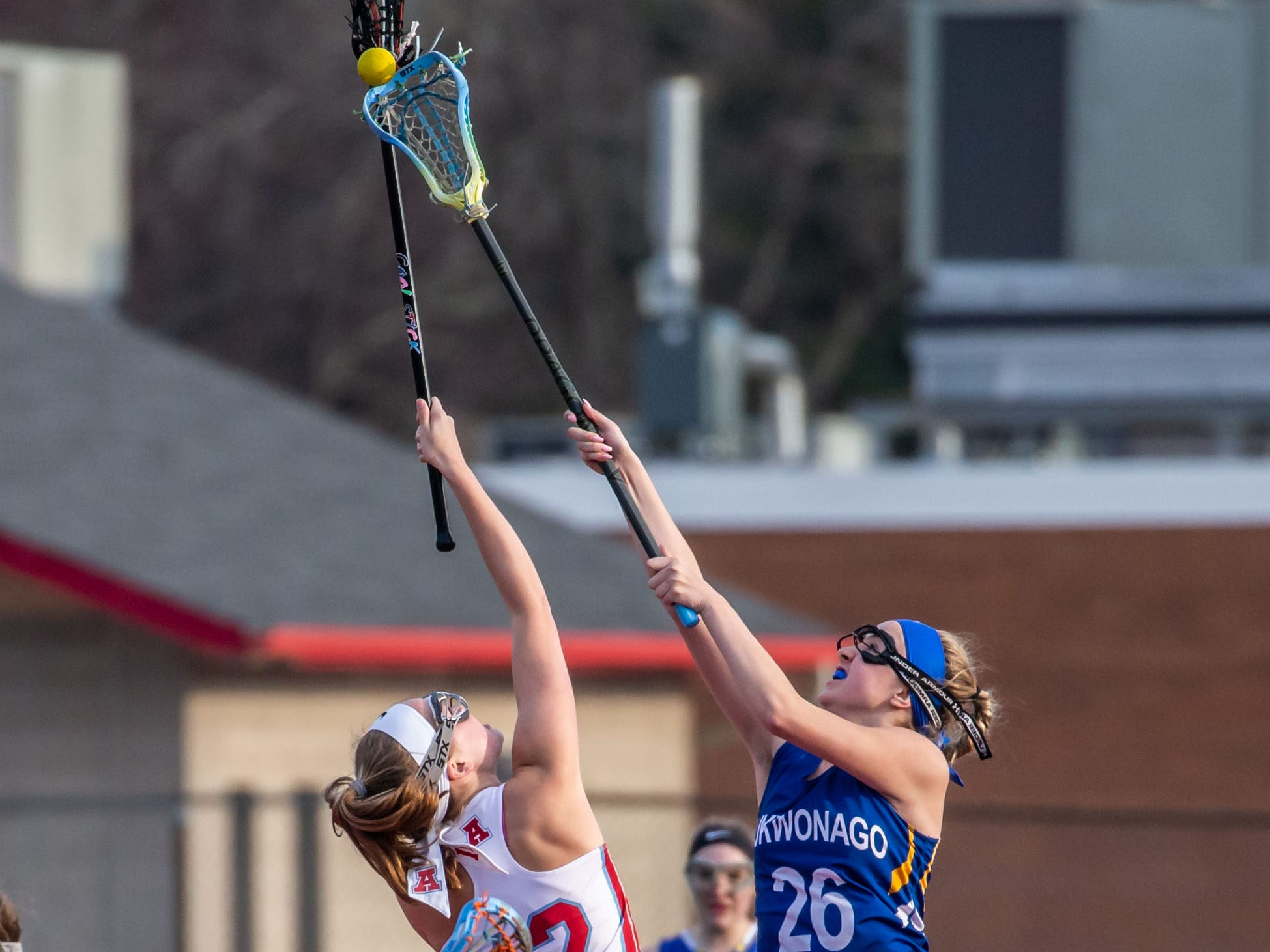 Arrowhead's Coryn Tormala (12) faces off with Mukwonago's Paige St. Clair (26) during the game at Arrowhead on Tuesday, April 16, 2019.