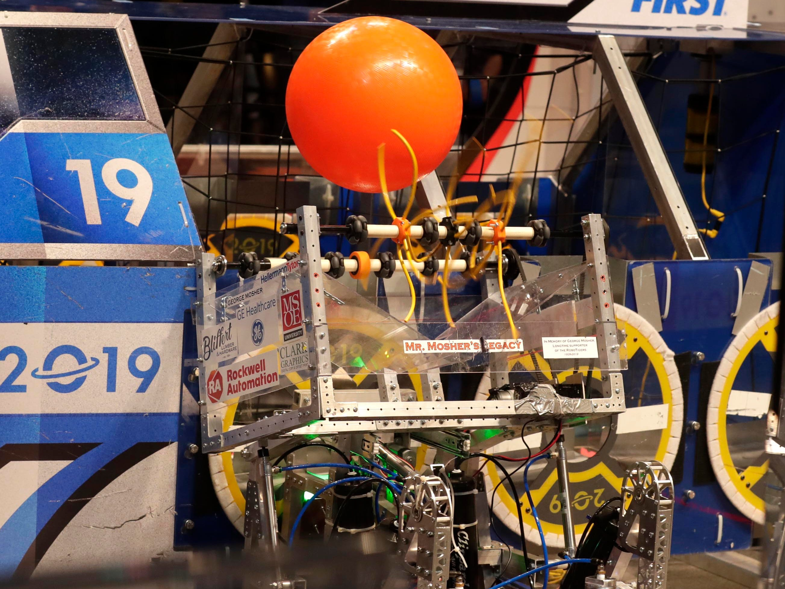Team members activate a spinning wire that moves a ball out of a basket into a hopper to score points during competition at the  U.S. First 2019 Wisconsin Regional Robotics Competition.