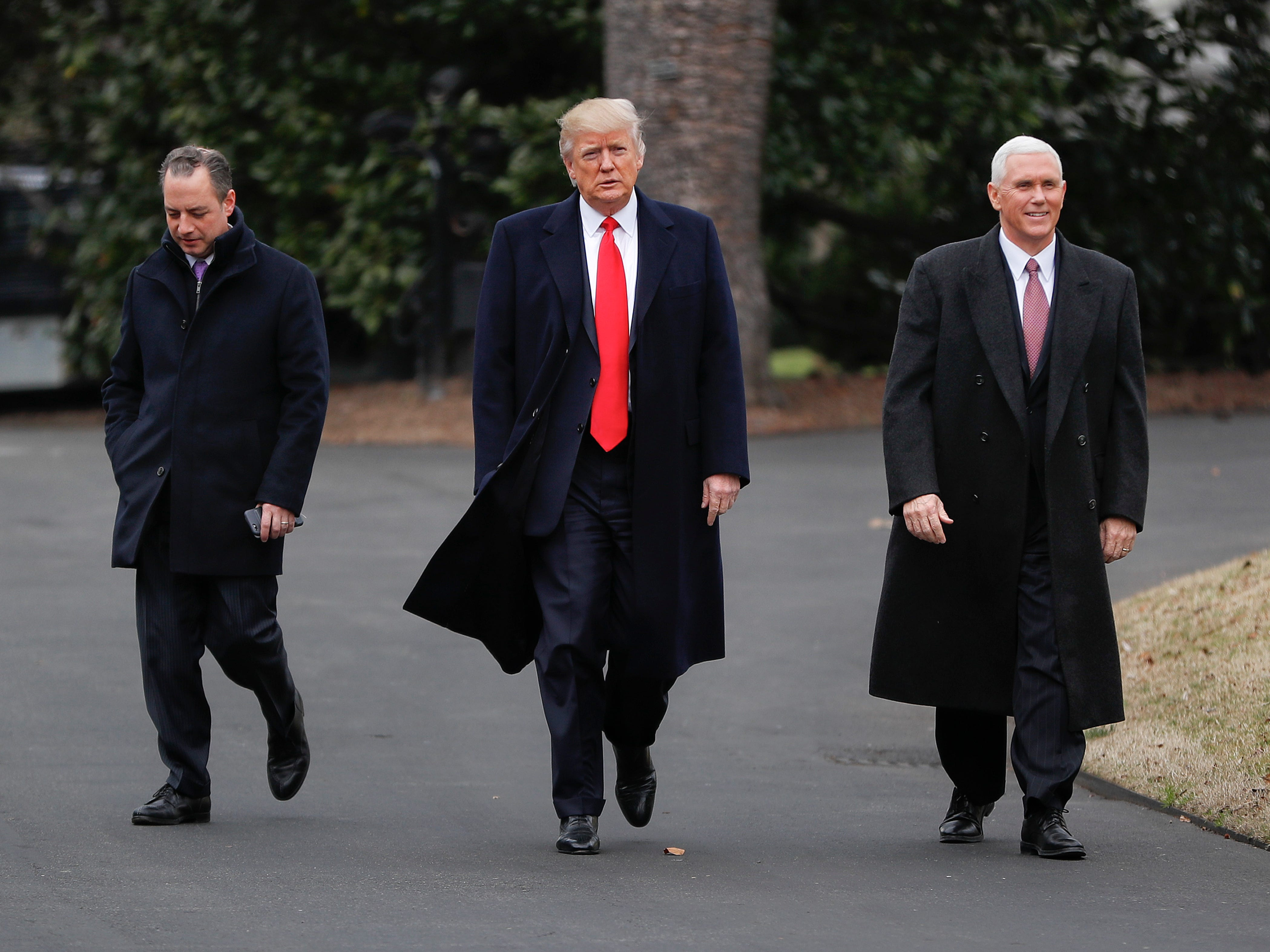 President Donald Trump (center), Vice President Mike Pence (right), and White House Chief of Staff Reince Priebus walk together on the South Lawn of the White House in Washington to greet Harley Davidson Harley Davidson executives and union representatives.
