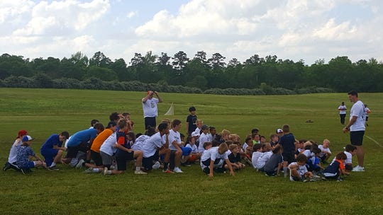 Former Auburn quarterback Jarrett Stidham (far right) speaks to kids after a camp at Wire Road Sports Complex on Sunday, April 14, in Auburn, AL.