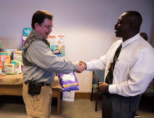 "Reporter Marty Roney receives some diapers from Eric Morris, juvenile probation officer, as he hosts a ""baby shower"" to benefit the River Region Pregnancy Center  in Prattville, Ala., on Wednesday, April 17, 2019."