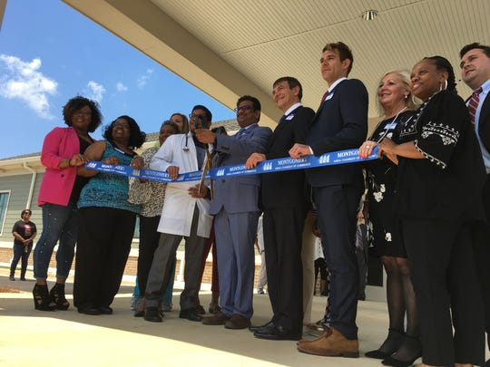 Physicians Choice Dialysis employees prepare to cut a ribbon at the opening of their new Montgomery facility.