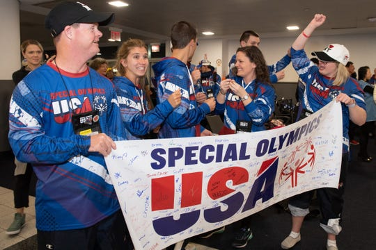 Taegan Martin, right, celebrates with her team as they prepare to board a 14-hour flight to Abu Dhabi in New York City in March 2019.