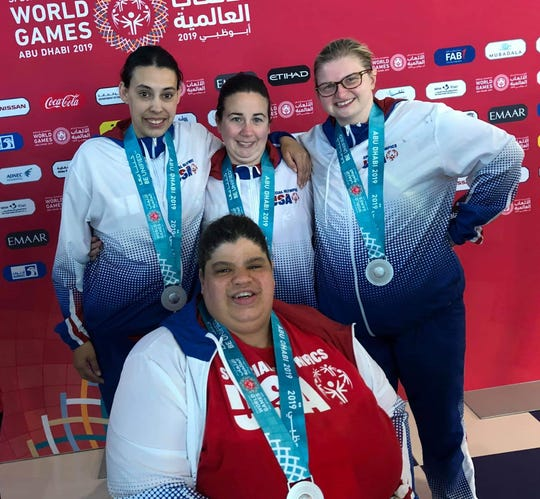 Taegan Martin, right, and her teammates pose with their silver medals. Their win came one day before the games ended. They placed second to the team from Panama.
