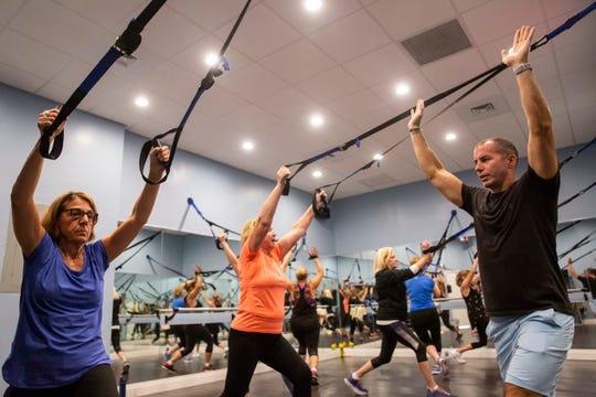 Stan Schoenewald, right, instructs Trish Conway, left, during a TRX, or total body resistance exercise, class at Kensington Country Club fitness center in Naples on Monday, April 15, 2019. Schoenewald, a recovering alcoholic, went through the Justin's Place Recovery Program at St. Matthew's House after attempting suicide in December 2014. With the help of a grant through St. Matthew's House, Schoenewald got certified as a personal trainer and now works at Kensington, Wyndemere Country Club, and the Greater Naples YMCA.