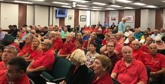 Residents, many from Tuscany Cove wearing red, attend a planning commission meeting Thursday, April 18, 2019, to discuss a proposed mixed-use development at the intersection of Collier Boulevard and Immokalee Road.